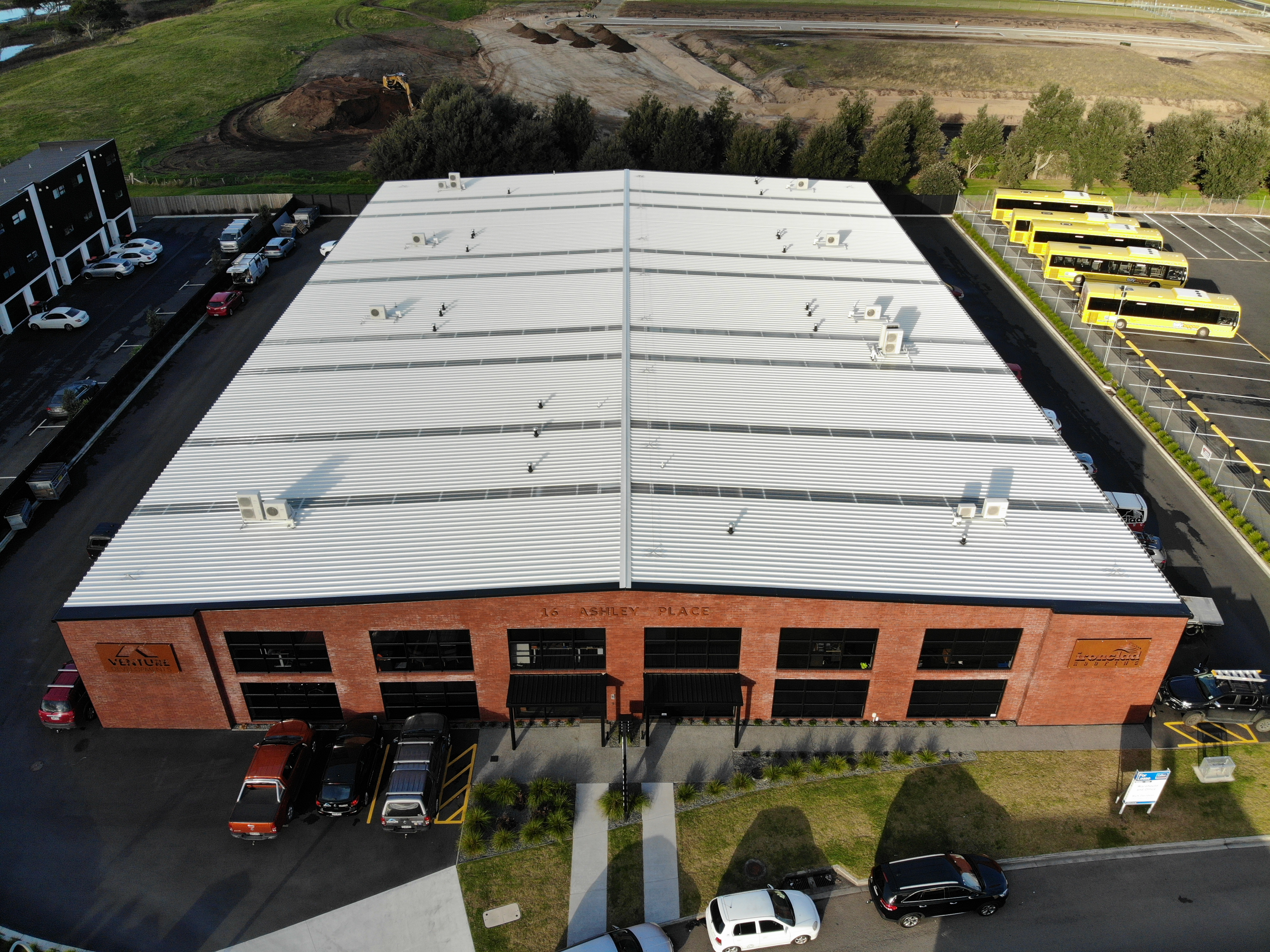 An aerial view of a large commercial building set in an industrial area, with most of the photo showing the new roof